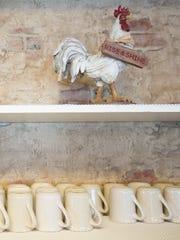 A chicken figurine sits above a shelf of coffee mugs