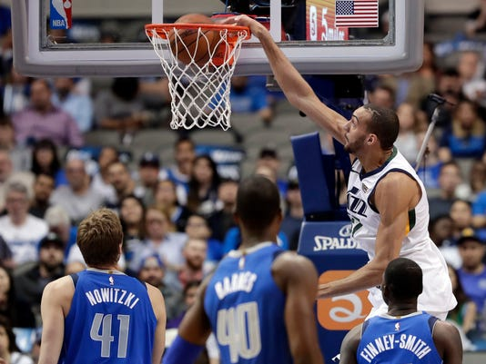 Utah Jazz center Rudy Gobert (27) dunks as Dallas Mavericks' Dirk Nowitzki (41), of Germany; Harrison Barnes (40); and Dorian Finney-Smith, right, watch during the first half of an NBA basketball game Thursday, March 22, 2018, in Dallas. (AP Photo/Tony Gutierrez)