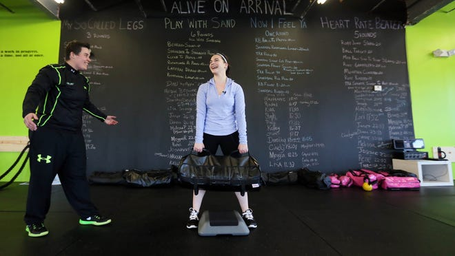 Health reporter Jen Rini lifts 45lb bags with the coaching of Missy Muller, owner of Done Done Fitness in Middletown for Move it DE.