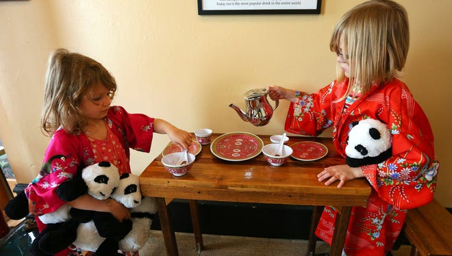 Audi Evans, 5, and her sister Mara Evans, 7, have a tea part inside the China Room exhibit at Gilbert House Children's Museum.