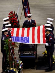 The honor guard folds the flag from the casket of Lansing Fire Department Firefighter Dennis Rodeman during funeral services for Rodeman in the Breslin Center on the MSU campus Wednesday.  The funeral drew a huge turnout of firefighters and others from around the state and country.  Rodeman died in LLansing last week after being struck and killed by an irate driver while Rodeman and other firefighters were collecting donations for charity.