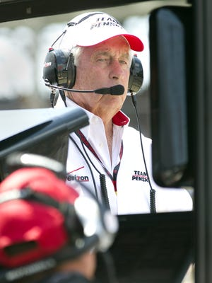 Team owner Roger Penske looks at the timing ans scoring monitor on his pit box Sunday at the Indianapolis Motor Speedway.