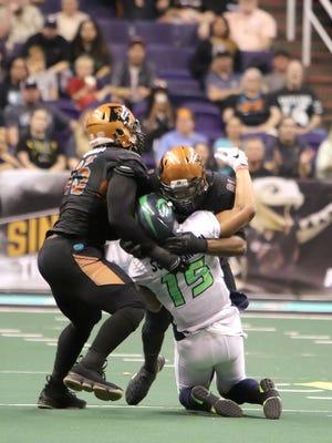 Nebraska Danger quarterback Jesse Scroggins gets hit by the Rattlers defense during Saturday night's game at Talking Stick Resort Arena.