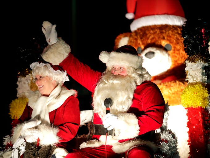 Santa Claus and Mrs. Claus wave to the crowd during