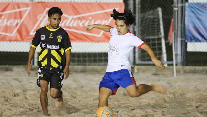 Quality Distributors' Jared Pangindian winds up to send the ball forward past Bobcat Rovers' Joseph Kim in a LandShark Beach Soccer League playoff match Wednesday evening at the Guam Football Association National Training Center beach soccer court. Quality won 5-2.