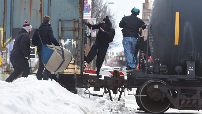 Pedestrians climb between two train cars after the train got stuck on the tracks around 11 a.m. along North George Street on Friday.  The York City Fire department said that North Beaver, North George and North Queen streets were blocked after two of the train's wheels came off the track.