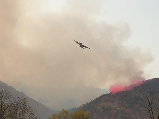 A C-130 tanker plane dumps slurry on a fire on Neddy Mountain in Cocke County