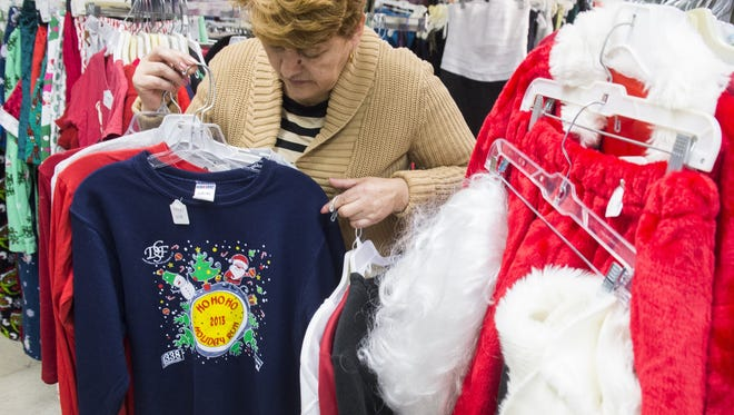 """Irene Lopez, manager of Frugalista second hand store, shows off the store's supply of """"ugly"""" Christmas sweaters in Washington, DC, December 23, 2014."""