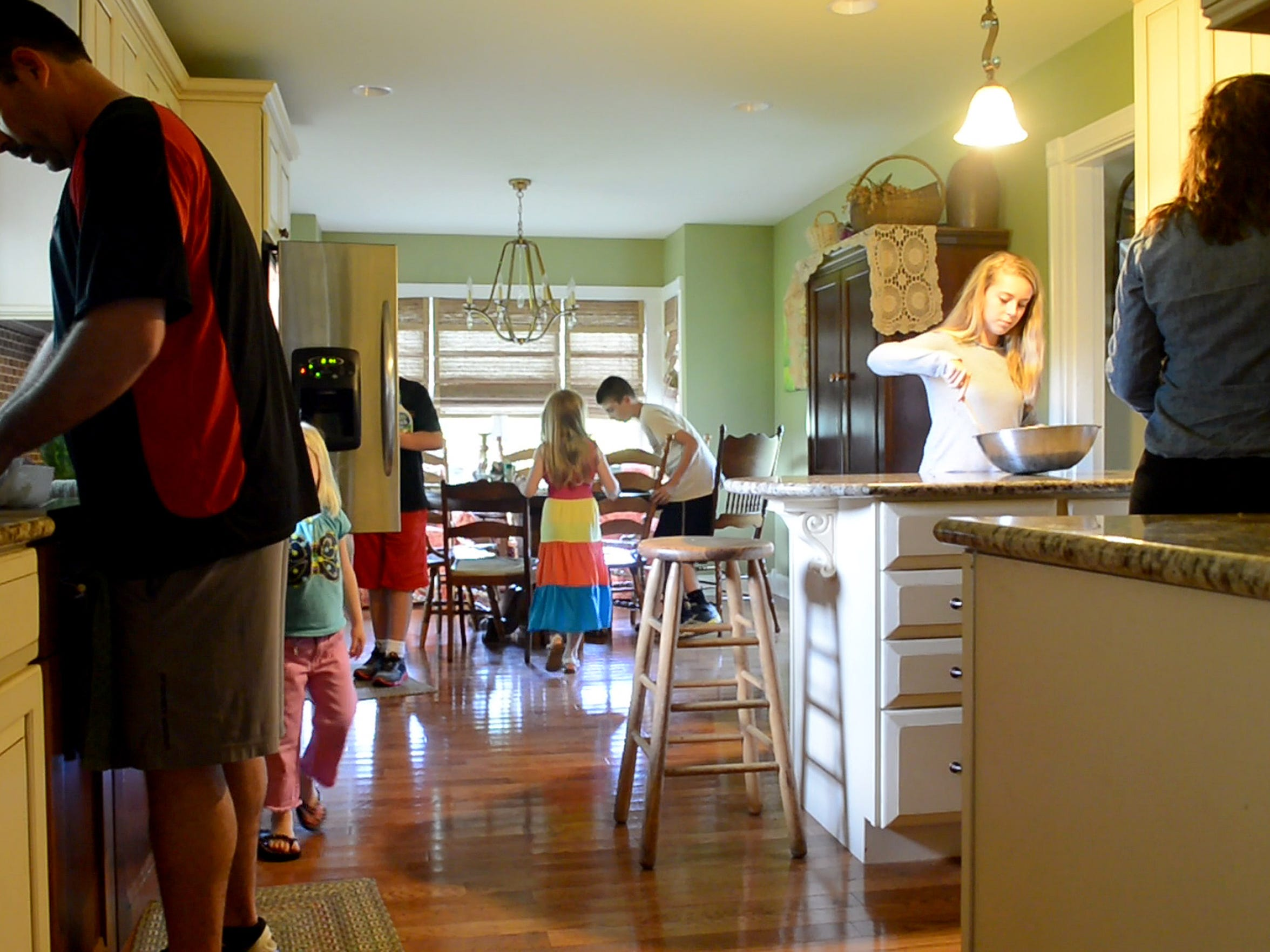 Mary Jordan (right), 14, works with the salad as her family prepares for dinner at their family home near Waynesboro on Monday, May 20, 2013.  Both Jeff and Lisa Jordan's natural born and adopted children come together to form one family.
