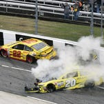Drivers Joey Logano (22) and Matt Kenseth tangle during the NASCAR Sprint Cup race at Martinsville Speedway in Martinsville, Va.