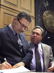 Rep. Jerry Torr, R-Carmel, right, confers with Rep. Sean Eberhart, R-Shelbyville, before Eberhart made his closing comments on the bill to allow firearms in school parking lots. The House joined the Senate in passing the measure on the last day of this year's Indiana General Assembly, Thursday, March 13, 2014. The House voted 75-24 to allow them.
