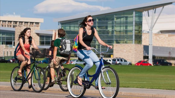 Colorado State University Students ride bikes on campus with the Student Recreation Center in the background. (Photo courtesy Colorado State University)