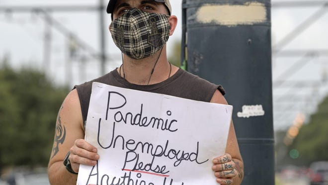 Sean Harris holds a sign asking for help last week in New Orleans. Harris had just completed training to be a haunted history tour guide in the French Quarter when the coronavirus pandemic hit. He has not been able to find a job since.
