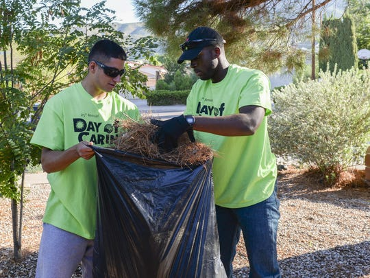 Airmen 1st Class Michael and Michael, Day of Caring volunteers, who are both heating, ventilation and air conditioning technicians with the 49th Civil Engineer Squadron here, gather pine needles from a disabled resident's front lawn in Alamogordo, N.M. on Sept. 9, 2016. The annual Day of Caring volunteer event helps disabled individuals and senior citizens within the Otero County community. (Last names are being withheld due to operational requirements).