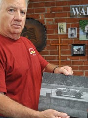 Joe Raines holds a news photo of race car driver, Wichita Falls native, George Barringer. A tribute car to Barringer was unveiled Friday morning and will be on display at Patterson's Crazy Car Museum, located on Midwestern Parkway.