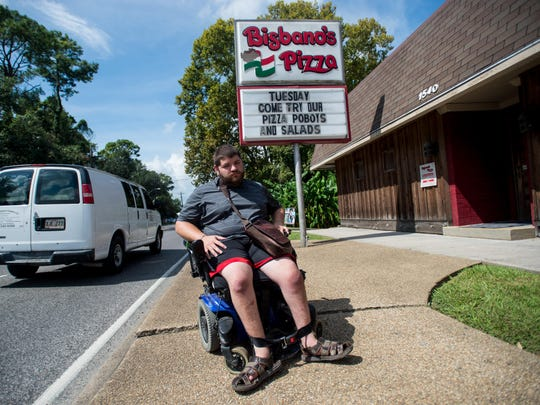 Liam Doyle drives his wheelchair near the front entrance at Bisbano's Pizza in Lafayette. Doyle and the nonprofit Advocacy Center of Louisiana are suing Bisbano's Pizza for non-compliance with the Americans with Disabilities Act.