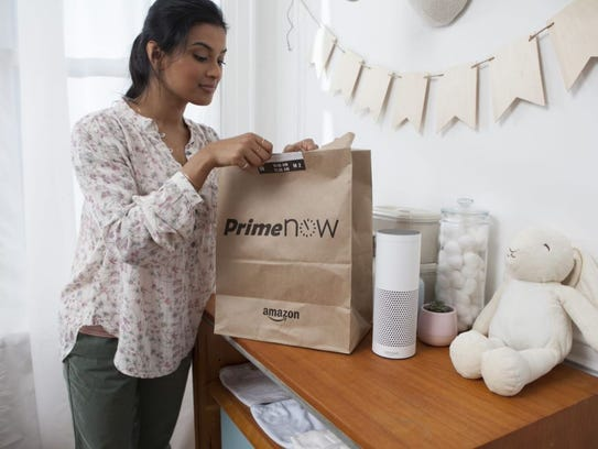 A customer inspects an Amazon Prime Now delivery.