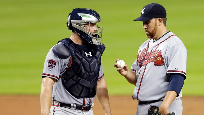 Atlanta Braves starting pitcher Aaron Harang talks with catcher Evan Gattis during the third inning after giving up five runs in the first three innings.