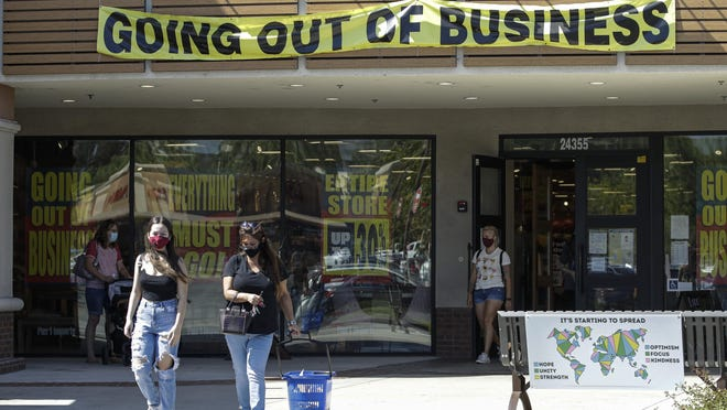 Shoppers walk outside of a Pier 1 Imports store as going out of business signs are posted amid the coronavirus pandemic Wednesday, July 1, 2020, in Santa Clarita, Calif.