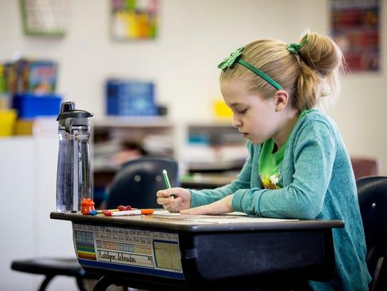 Katelynn Schneider, 10, works on a spelling test Friday,