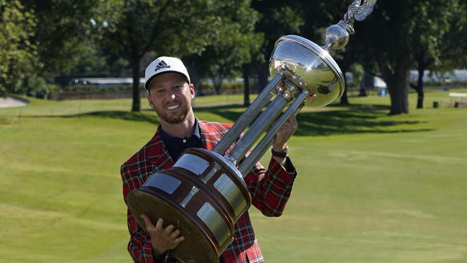Daniel Berger holds the winner's trophy of the Charles Schwab Challenge golf tournament after a final-round playoff Sunday against Collin Morikawa at Colonial Country Club in Fort Worth, Texas.