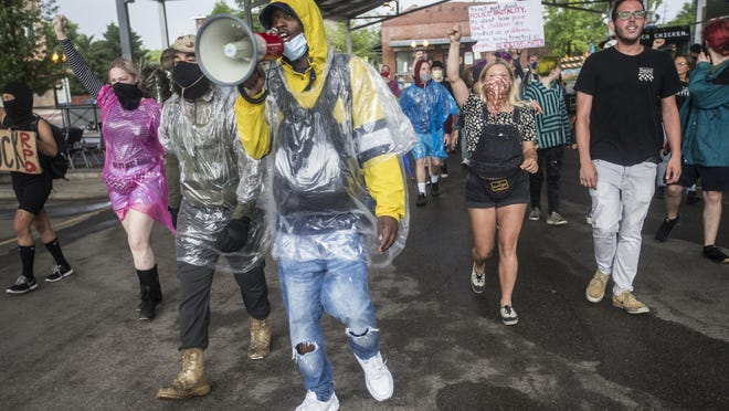 Rockford Youth Activism spokesman Leslie Rolfe, center, leads protesters on a People's Mic march through City Market on Friday, June 26, 2020, in Rockford.