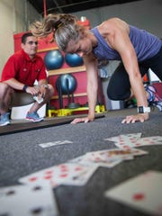 Nic DeCaire of Fusion Fitness and Leigh Anne Emrich, of Newark, demonstrates the House of Cards workout using playing cards and your body weight.