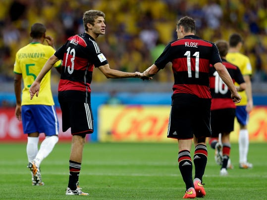 Germany's Thomas Mueller (13) is congratulated by teammate Miroslav Klose (11) after scoring his side's first goal during the World Cup semifinal soccer match between Brazil and Germany at the Mineirao Stadium in Belo Horizonte, Brazil, Tuesday, July 8, 2014. (AP Photo/Natacha Pisarenko)