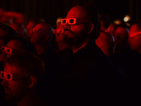 Concert goers wear 3D glasses as they watch a performance