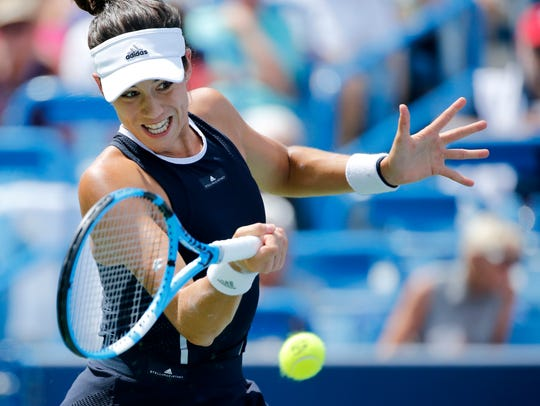 Garbiñe Muguruza returns a shot in the first set of