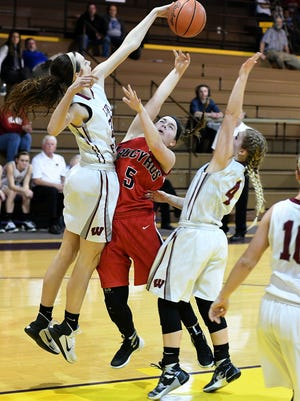 Bucyrus' Isidora Burling is met with some resistance from Lydia Wiers and Ashlee Tuttle of Willard on Wednesday night at Lexington High School during the first round of the Division III Girls' Sectional Basketball Tournament.
