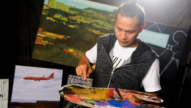Artist Marcial Pontillas demonstrates how he uses his palette knife when he creates his artwork during a photo shoot in Hagåtña on Thursday, Aug. 11.