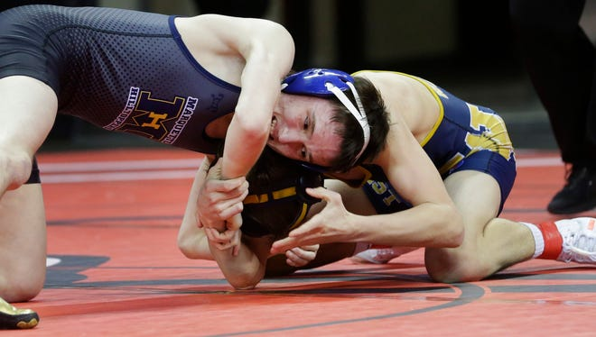 Marquette University High School's Tom Dineen (left) defeats Wausau West's Cameron Schmeiser during the division 1 quarterfinal round.