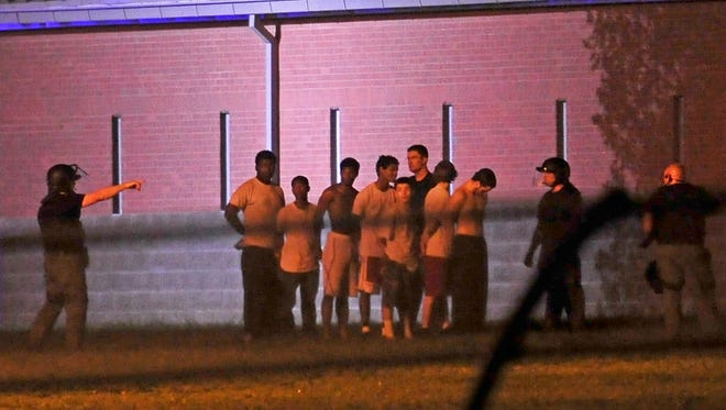 A group of teenagers is arrested by officers at Woodland Hills Youth Development Center in Nashville, Tenn., Thursday, Sept. 4, 2014.