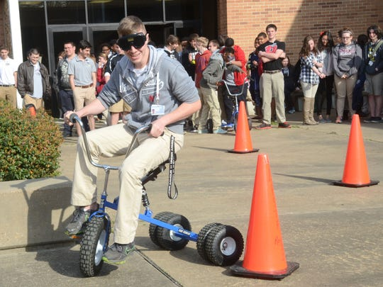 """Pineville High School sophomore William Goleman rides an adult tricycle while wearing """"drunk goggles"""" during a Sudden Impact seminar on Tuesday. Louisiana State Police, Rapides Regional Medical Center nurses and PHS senior Morgan Rollins held the seminar, which is part of Rollins' senior project."""