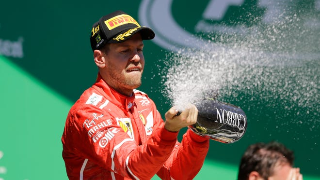 Ferrari driver Sebastian Vettel celebrates at the podium after winning the Brazilian Grand Prix.