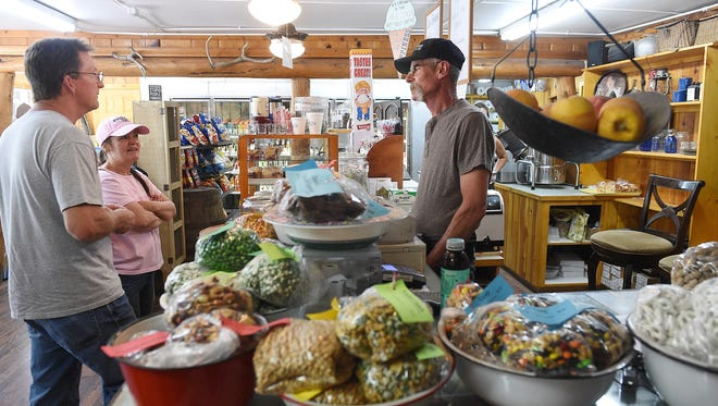 Rick and Pam Huseby of Nebraska talk with owner Steve Childs at the Glen Haven General Store on Thursday. Steve and his wife, Becky, are hopeful that business will pick up now that Larimer County Road 43 has fully reopened following the 2013 flood.