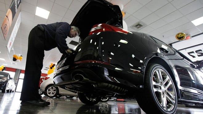 In this 2012 photo, a shopper checks out a Kia Optima at a Kia car dealership in Elmhurst, Ill. Auto Web sites — once filled mostly with reviews and advice — are getting more sophisticated, connecting potential buyers with dealers and offering instant price guarantees.