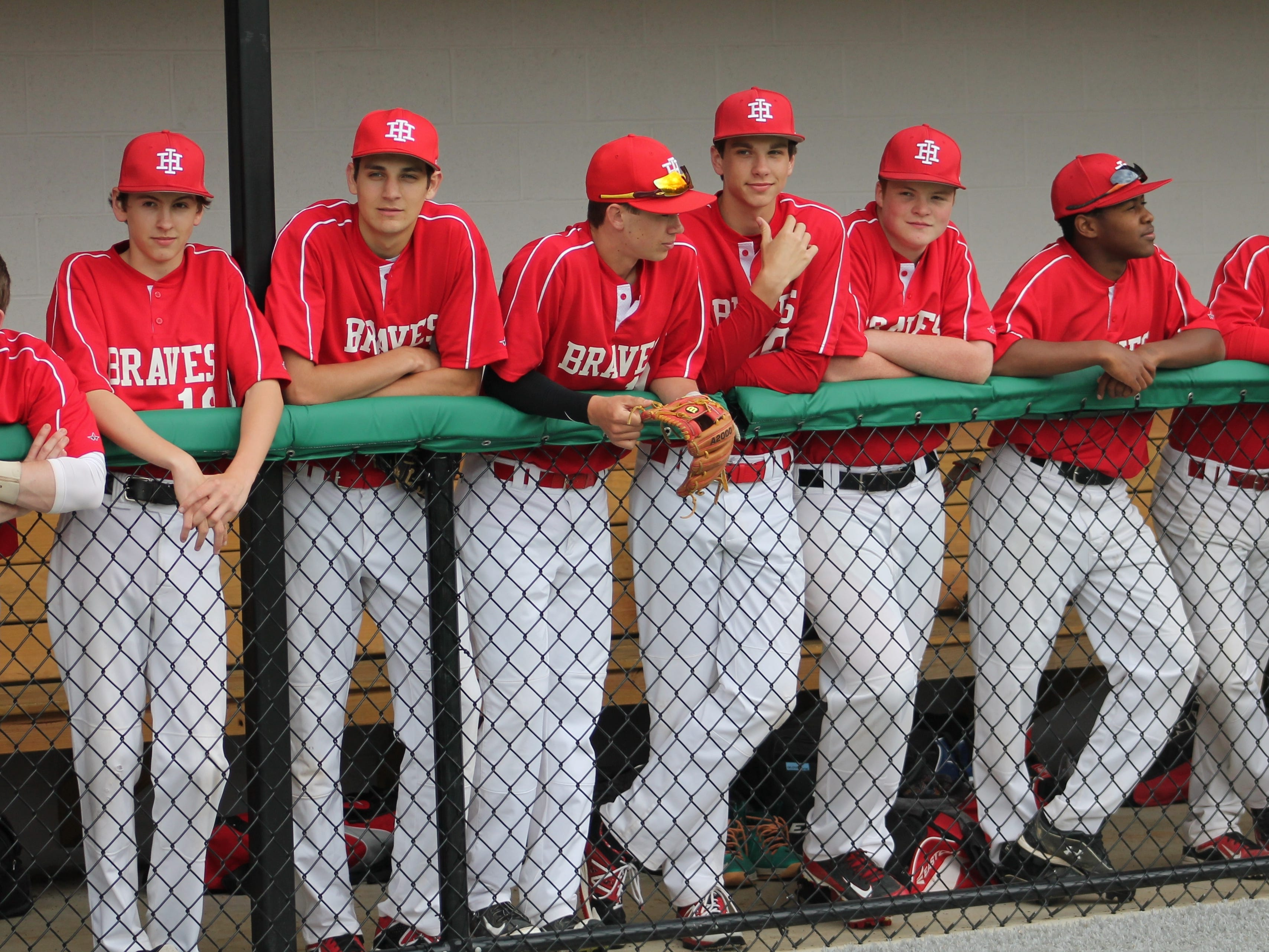 Indian Hill players line the dugout to take in the dedication ceremony of the school's new baseball/softball complex April 20.