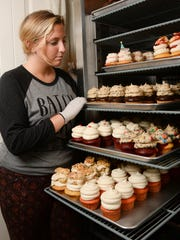 Brandi Lindoe of Clemson Confectioneries checks over her decorated cupcakes at her townhouse in Clemson on Thursday.