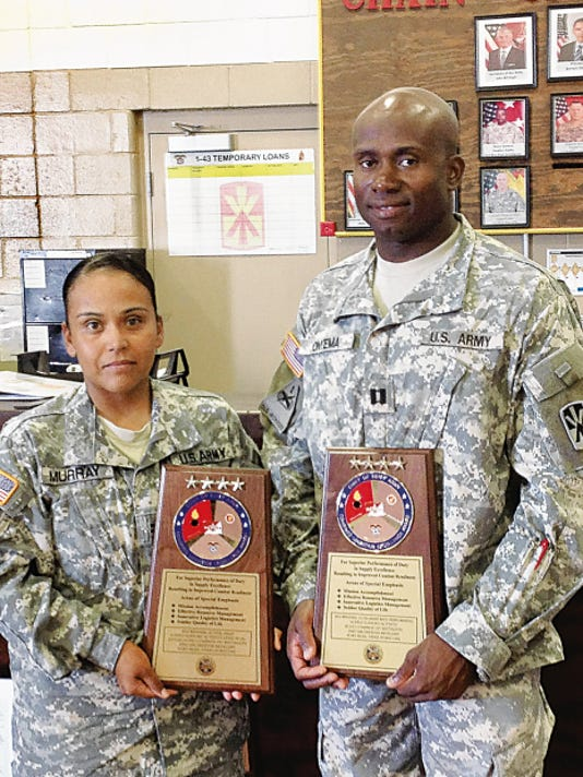 Chief Warrant Officer 2 Faith G. Murray, left, and Capt. Kingsley C. Onyema show off the Army-wide awards Echo Company won for excellence with its warehouse operations.