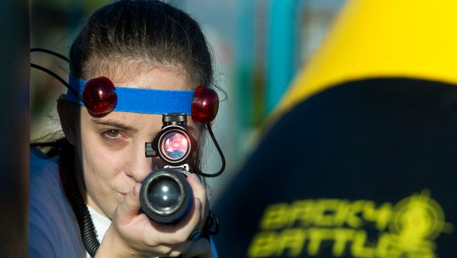 Aylin White takes aim with her M5 Stinger under cover of a inflatable laser tag bunker at Sam Graft Park Monday, Aug. 15, 2016. The weapon and bunker are part of the Back40Battles Mobile Combat LaserTag arsenal.