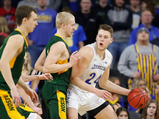 A.J. Jacobson #21 of North Dakota State bodies up on Mike Daum #24 of South Dakota State at the 2018 Summit League Basketball tournament at the Denny Sanford Premier Center in Sioux Falls.