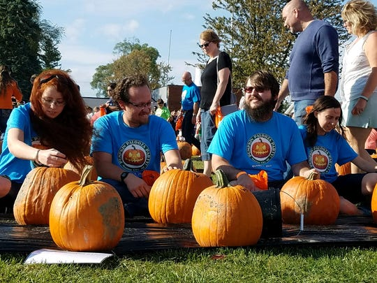 A team of carvers await the signal to start carving pumpkins on Saturday, Oct. 7, 2017, at Nautical Mile Park in Marine City.