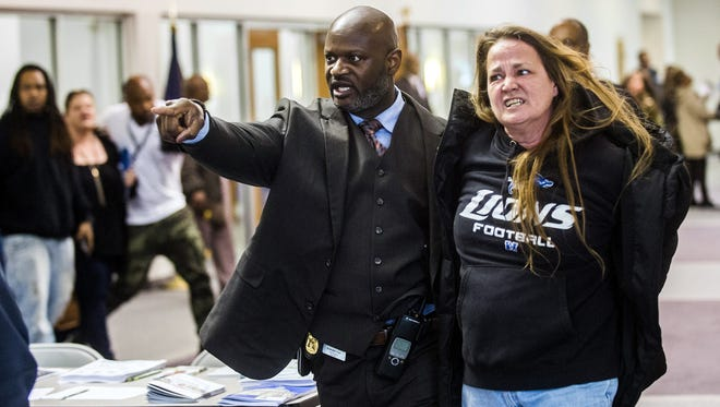 Flint police officer Kristopher Jones removes resident Leah Palladeno, in handcuffs, from a town hall meeting at House of Prayer Missionary Baptist Church, related to the city's crisis with lead-tainted water, in Flint, Mich.