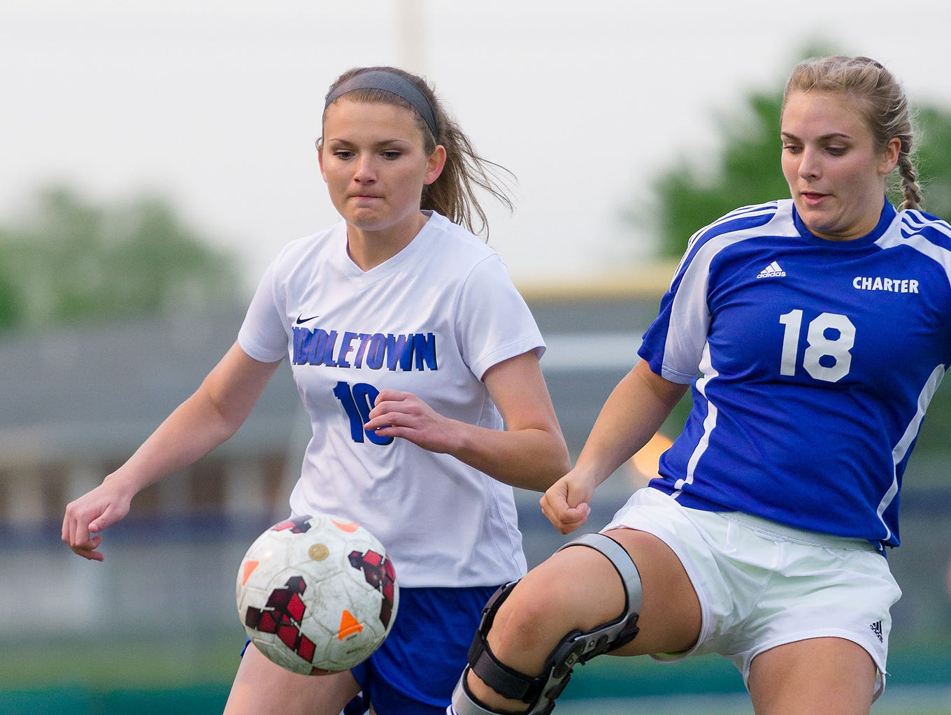 Taylor Mitchell (18) of Charter and Kelsey Hott compete for control of the ball in a Charter at Middletown girls soccer game on Wednesday.
