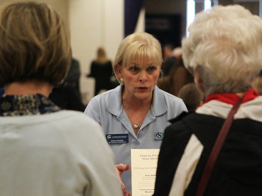 File photo - Paula Holden, a liaison with Senior Medicare Patrol with the California Health Advocates, center, talks to people in 2016 at the Shasta County District Attorney's Office's Fraud Prevention fair at the Veterans Hall in downtown Redding. (Andreas Fuhrmann/Record Searchlight)