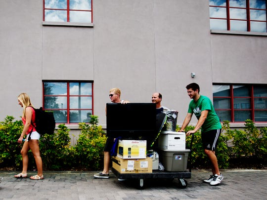 Dan Vicinanzo, right, a senior at Ave Maria University, helps Matt Olenek and his family move into the dorms o Thursday.