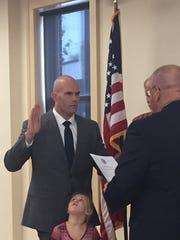Benjamin Sholl, left, is sworn in as Newark Police Officer as his daughter, Arabella, looks on.