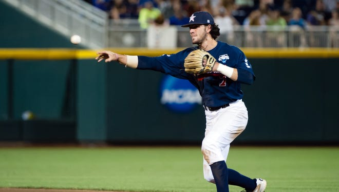 Jun 23, 2014: Vanderbilt Commodores infielder Dansby Swanson (7) makes the throw to first base against the Virginia Cavaliers during game one of the College World Series Finals at TD Ameritrade Park Omaha. Vanderbilt defeated Virginia 9-8.